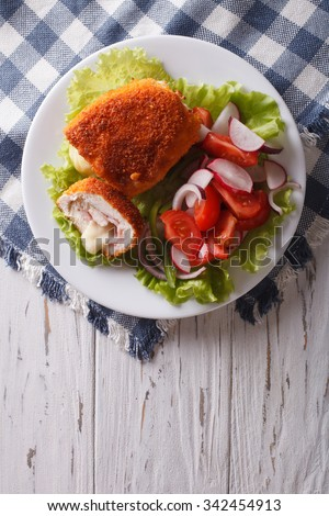 Chicken schnitzel cordon bleu and a salad on a plate on a table. vertical top view - stock photo