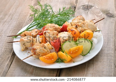 Chicken shish kebab on wooden table - stock photo