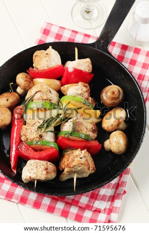 Chicken shish kebabs and mushrooms in a pan - stock photo