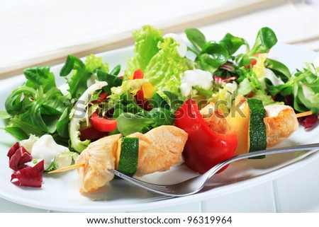 Chicken skewer with spring salad - stock photo