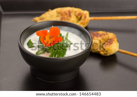 Chicken skewers and bowl of sauce on a black plate. - stock photo
