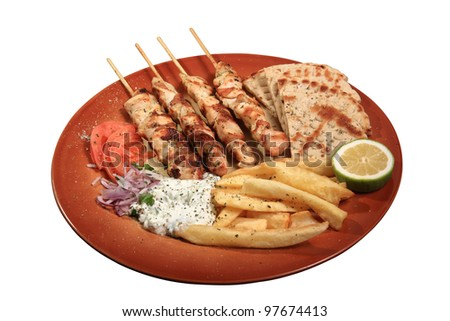 chicken skewers served on a plate with fries tzatziki and pita - stock photo