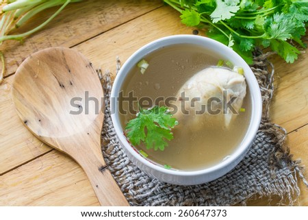 Chicken soup, chicken soup in a cup with a sack on the table. - stock photo