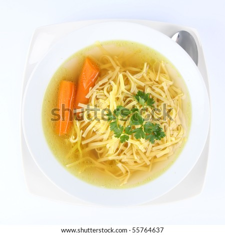Chicken soup with macaroni and carrots decorated with parsley on a plate with a spoon - stock photo