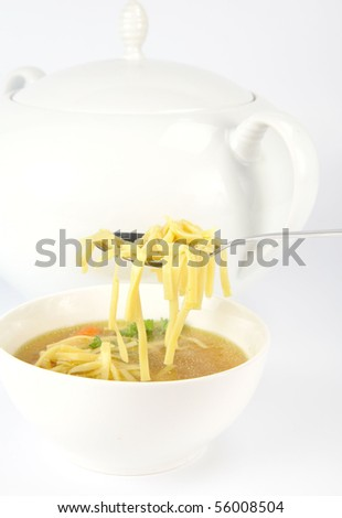Chicken soup with macaroni and  decorated with parsley in a bowl, some on  a spoon, with soup tureen in the background - stock photo