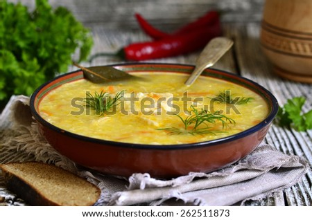 Chicken soup with millet and vegetable in a clay bowl. - stock photo
