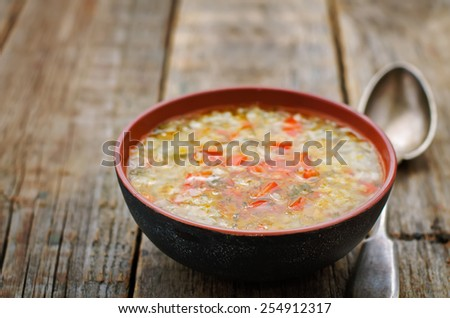 chicken soup with rice and peppers on a dark wood background. tinting. selective focus - stock photo