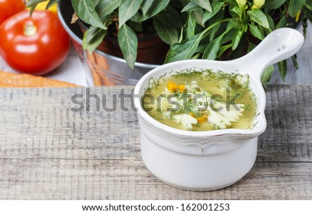 Chicken soup with vegetables on wooden table. Copy space. Your recipe here - stock photo