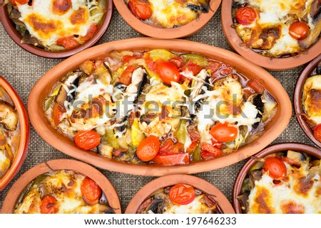 Chicken stews in stoneware cups served together on the table, oval big stew surrounded with several small round stoneware crock cups - stock photo