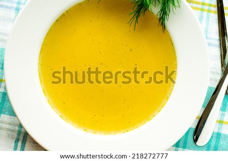 Chicken stock, bouillon, broth, clear soup in a white plate - stock photo