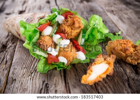 Chicken strips in a Tortilla Wrap with Lettuce on wood. - stock photo
