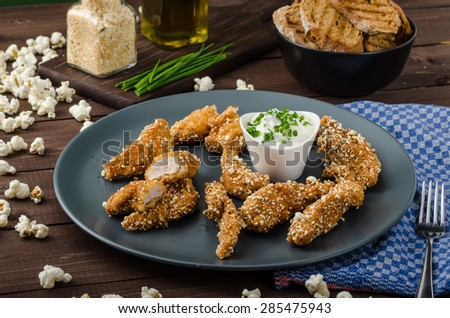 Chicken strips in popcorn breadcrumbs, with delicious garlic dip and panini toast - stock photo