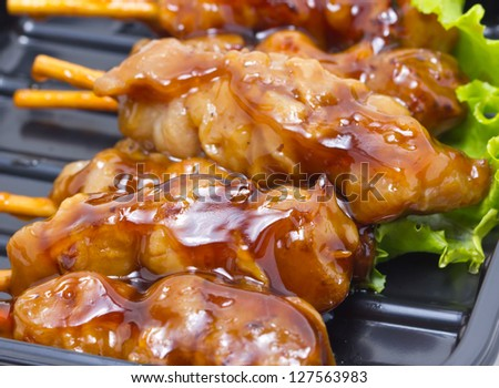 Chicken teriyaki with skewers in black tray. - stock photo