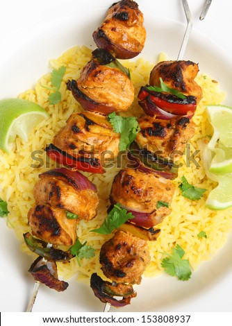Chicken tikka kebabs with red onions and peppers. - stock photo