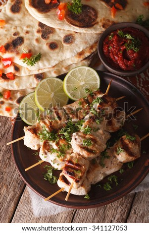 Chicken tikka skewers and naan flat bread with chutney sauce close-up on the table. vertical
