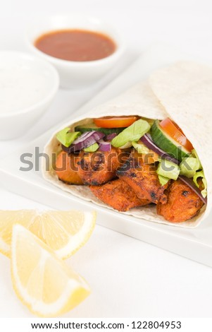 Chicken Tikka Wrap - Tandoori chicken tikka with salad wrapped in a flatbread, served with chili sauce, yogurt and mint raita and lemon wedges on a white background. - stock photo
