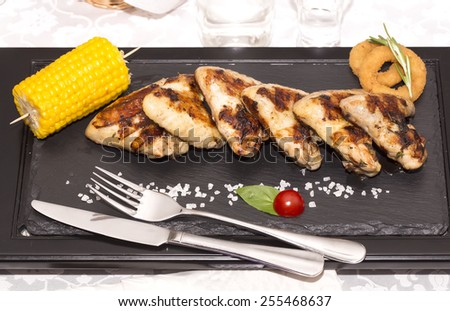 chicken wings are grilled on a wooden platter - stock photo