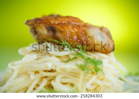 Chicken wings fried with noodles in a bowl - stock photo