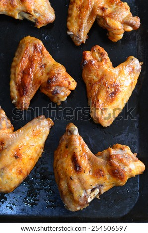 Chicken wings on baking tray, selective focus - stock photo