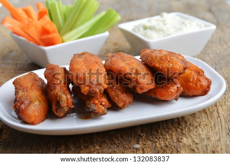 chicken wings with celery and carrot on wooden background - stock photo