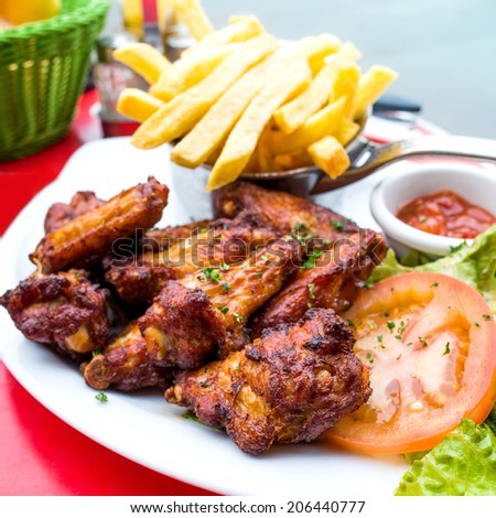 Chicken wings with sauce and golden French fries potatoes  - stock photo