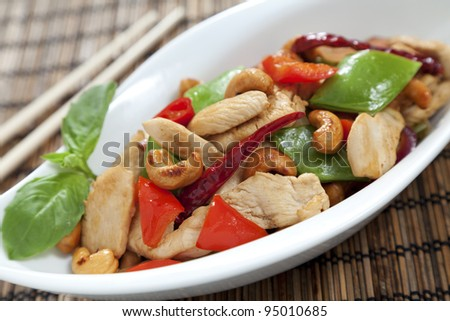 Chicken with cashew nuts, chili, capsicum and snow peas on a bamboo mat with chop sticks - stock photo