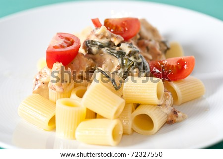 Chicken with pasta and fresh cherry tomatoes on a pastel tablecloth - stock photo