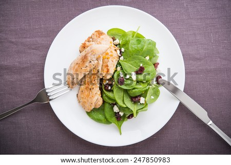 Chicken with spinach salad on dark background top view. Healthy food. - stock photo