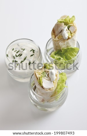 Chicken Wraps in glasses and Yoghurt dip in glass - stock photo
