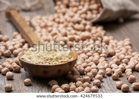 Chickpea flour in a wooden spoon, chickpeas on old wooden background - stock photo