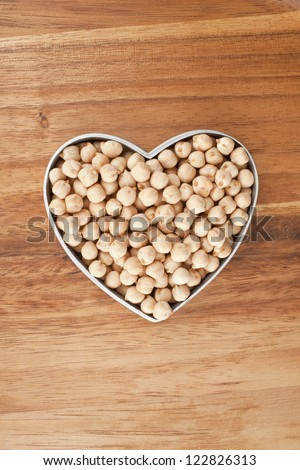 Chickpeas on a heart shaped bowl against wooden background - stock photo