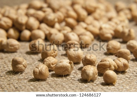 Chickpeas on natural brown fabric - stock photo