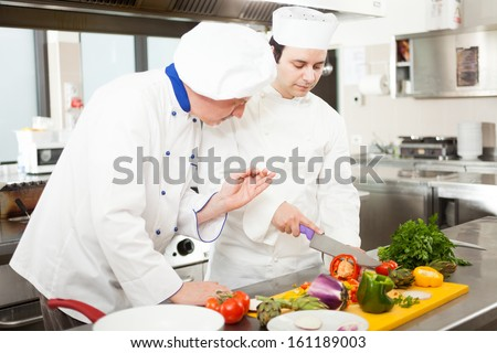 Chief chef watching his assistant cutting vegetables - stock photo