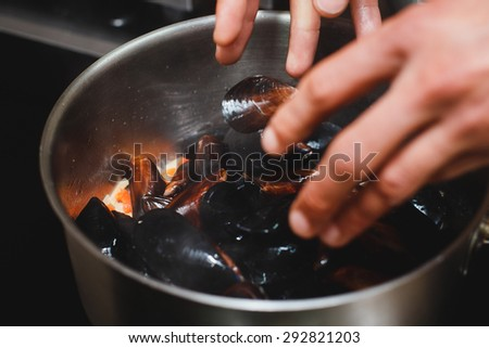 Chief cooking mussels - stock photo
