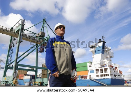chief engineer standing in front of large commercial-port as background, crane and ship - stock photo