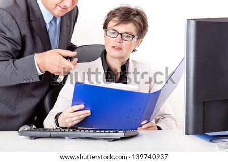 Chief looks together with staff in file folders - stock photo