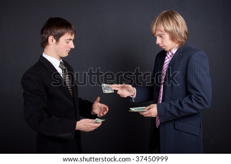 Chief pay out a salary. On black background. - stock photo