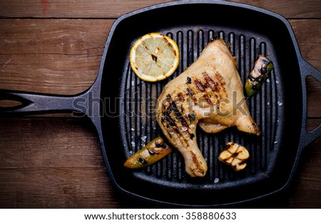 Chiken and vegetables on grill pan on old wooden table or board. Toned. - stock photo