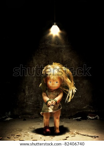 Child abuse - a doll in a dark room with hands tied and mouth sealed - stock photo