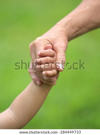 Child and grandma holding hands closeup - stock photo