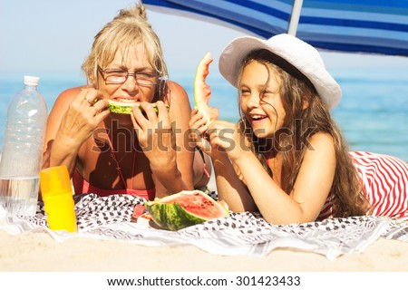 child and grandmother eating watermelon on the beach - stock photo