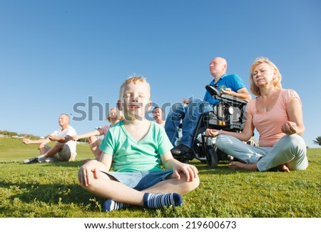 Child and Group of People with Disabled Man practicing yoga. - stock photo