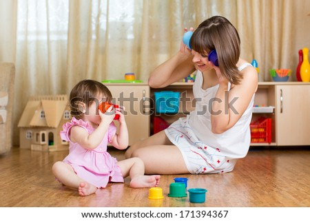 child and her mother playing together with toys - stock photo