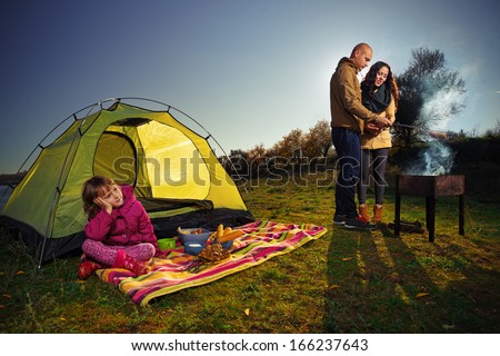 Child and her parents are cooking grilled shish kebab outdoor - stock photo