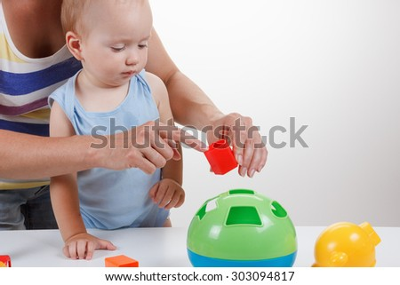 Child and Mother playing with toys in a blue dress smiling Studio - stock photo