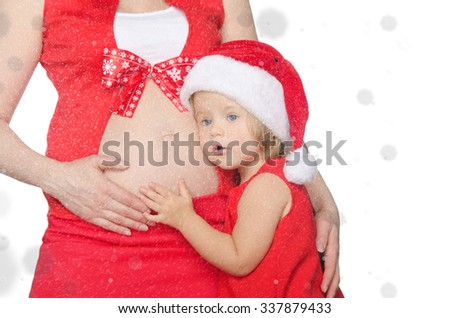 child and pregnant woman in Christmas clothes and snowflakes - stock photo