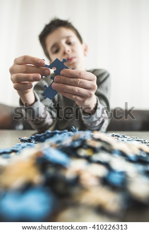 Child and puzzle. Pile puzzles - stock photo