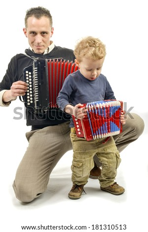 child and young man playing the accordion on the white background - stock photo