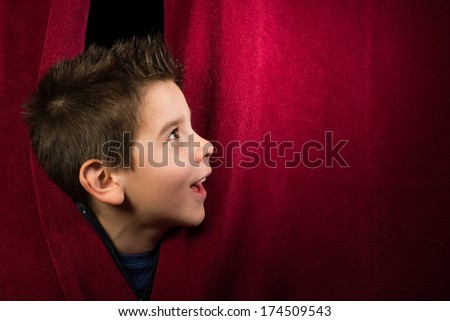 Child appearing beneath the curtain. Red curtain. - stock photo