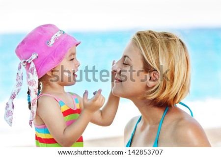 Child applying suntan  lotion to her mom and having great time together - stock photo